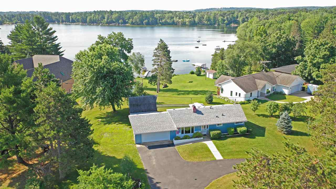 Peaceful lake views without paying for it!!! Charming ranch home with vaulted ceilings, dining area in kitchen, nice deck with gazebo, partially fenced in yard and partially finished basement. Home is in great condition with many updates  including: a newer furnace and central air, roof, drilled well, hot water heater deck boards, garage door & blacktopped horseshoe driveway. Property is located less than a 1/4 mile from a public boat landing to a great fully recreational Spencer Lake!  Large yard and driveway to keep your boat when your not using it on the lake! LOCATION, LOCATION, LOCATION!!