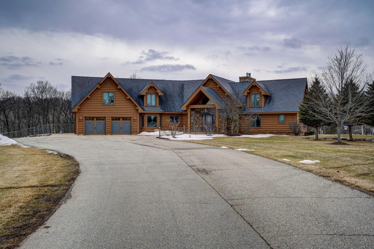 Wisconsin Dream Log Home living at its best!!This luxury 6,232 sq ft stunning log-sided home is situated on the edge of Burlington on 12.2 acres of which 7.2 acres are Productive Forest Land.Main home features 4 bedrooms/4 baths, Master is on the main level with ensuite and cathedral ceilings.  2 Gorgeous stone fireplaces, 2 sun rooms, upper bonus room, loft area, finished walk out basement with custom bar and entertaining areas, large balcony overlooking the massive in-ground pool with commercial slide and more! One outbuilding features a separate heated business office and separate apartment with plenty of room for your toys and a huge workshop with loft.  2nd outbuilding will hold large boats or RVs as well as plenty of work area. Your views are stunning all year long!