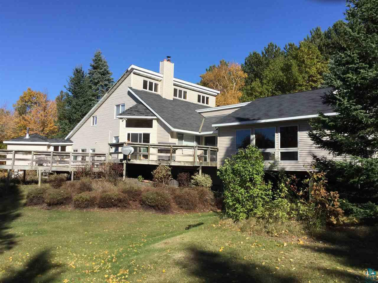 Spectacular west facing views of Lake Superior. Less than an hour commute to Superior & Duluth. This spacious home offers privacy located just outside Port Wing near Lake Superior & the Port Wing Marina on 30 forested acres. The main floor features an open living room/dining room/ kitchen, an added spacious family room with fireplace , second dining area & bar,a main bedroom, laundry room, attached two car garage, sauna & hot tub room, lots of closet space, & walk out decks. Gorgeous lake views from the second floor which features two bedrooms, an office space, & a bathroom.  The walkout basement features a bathroom, utility room, several rooms currently used as a bedroom, rec room, & den. The outside features gravel driveway, maintenance free exterior, decks, & fenced in gardens. There is  a large 26x 42 + 20 x 22 Pole Barn with two garage doors & a large sliding door, wood stove for heat, concrete floor, electricity, and a workshop area.  There is a 16 x 36 concrete pad with a shelter logic cover for RV storage.