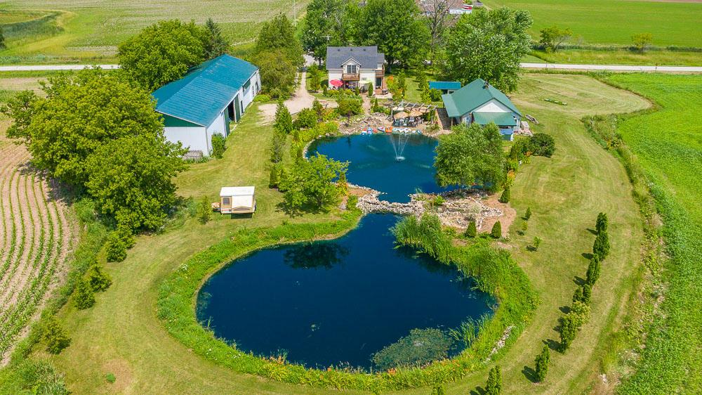 This beautifully landscaped destination is well suited for any dream you have! The property features two beautiful 25' and 35' deep spring fed ponds with fountain and beachfront that will make you never want to leave. The farmhouse kitchen has one of a kind original hand routed trusses & cedar beams and also has a second kitchen upstairs. First floor master bedroom and full bath. HUGE 40' X 120' Pole Barn. There is also another Mennonite building with electric, sewer and water that has already been in the makings for 2 separate living quarters, and lofts to rent as a bed and breakfast. 25 Minutes away from Whistling Straits Golf Course, which is the home of the Ryder Cup. Truly one of a kind property! Book your showing today!