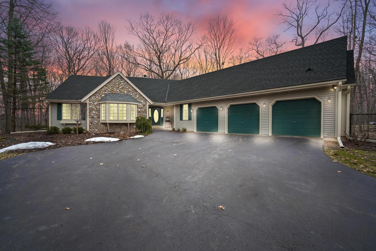Nestled in a wooded cul-de-sac this stunning ranch is tucked in on a beautifully landscaped wooded 1.98-acre lot. The inviting foyer greets you with a delightful open concept great room, dining room and gourmet chef's kitchen with vaulted ceilings, maple hardwood floors, enveloped by the enchanting views from the wall of windows. Entertain family & friends with delight as you prepare the finest feast in your gourmet chef's kitchen with granite counter tops & kitchen island.  Lower level features a full bath, bedroom, sauna, 2nd laundry, Rec Room with pool table, impressive lannon stone fireplace with walkout basement & patio. Enjoy a cozy evening, retire to your tranquil master suite with master bath and walk-in closet with peaceful views at the end of the day. Welcome to your Dream Home!