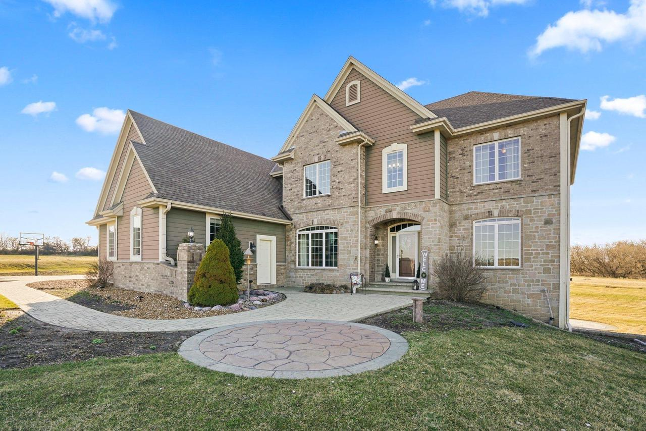 Custom built Executive home on 2+ acres in Stone Creek Crossing! Inviting Foyer introduces over 5,000 sqft of living space enhanced by an Open Concept flr plan w/HW Floors, Arch Doorways & 2 panel doors! Eat-In Kitchen w/breakfast bar & Island overlooks Living Room w/floor to ceiling windows & updated Fireplace.  Dining Rm, Bedroom w/Bath, Office, 1/2 Bath &  Mudroom complete the 1st floor. Upper level includes Family Room & large Bonus Room off of Master. Luxury Master Bath offers a tile shower, jetted tub & huge WIC. BR 2 w/Bath & Addt'l BR's w/shared Bath. 2nd flr laundry. Walk-Out LL has tons of finishing potential! Fresh paint thruout & many new fixtures! Enjoy the convenience of a 4 car garage w/lift & basement access. 2 tiered deck & patio overlook expansive lot! Easy access to I-94