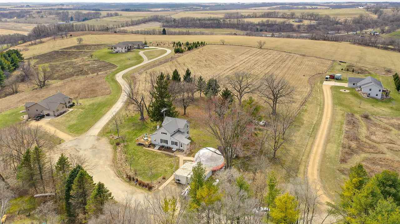 Majestic views: Updated farmhouse: 5.7 acres on a hill top with dramatic views over the beautiful drift-less area of Wisconsin. Just 25 minutes to Madison.  Includes 5 acre, fenced orchard of 500 trees, mostly apple, also cherry, peach and nectarine which should get to full production in 1-2 years and become quite a part time business.  On a secluded private cul-de-sac, the home exudes charm with repurposed barn wood, including beams and a beautiful barn door leading to your first floor owner suite complete with spacious en-suite full bath.  Home has a new metal roof & cedar deck.   An old wood stove provides heat to the whole house.  First floor laundry and 1 year Warranty. Upstairs, 3 very spacious bedrooms.  Good part time business for additional earnings. includes 30ft growing dome.