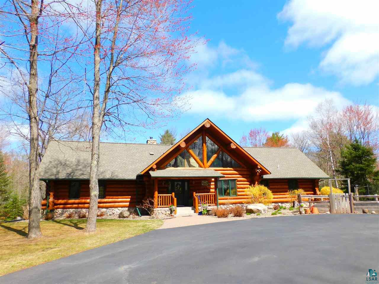 If you are looking to own a piece of Northern Wisconsin with a custom-built log home (Anderson & Hammack), nestle with mature Maple, Oak, Birch, Balsam, Aspen, Red Pine trees, and 1,600' of water frontage from Amnicon River. This property offers 58 acres of sandy soil, mature trees, a private & secluded setting with natural beauty and sounds that surround you. No matter what time of the year, this property has so much beauty to share with your family to create special memories. Imagine sitting outside on the balcony from the kitchen or in the front of this home under a covered front porch to watching wildlife or just listening to the sounds from Amincon River! Home includes many unique features to many to mention, vaulted ceiling with fans, two master bedrooms with two full master bathrooms, kitchen, dining room, ample storage, and lots of natural woodwork with large windows. The main floor features over-sized walls, vaulted ceilings with ceiling fans, and lots of double-paned windows will allow you to capture all the natural sunlight and views of beautiful trees and nature. Large wood-beamed ceilings throughout the living and dining room, and a unique curved stairway up to the upper loft area, that could be a possible sizeable fourth bedroom or Den/Family room. The kitchen includes hickory cupboards, granite countertops, gas stove, two ovens, with kitchenette & formal dining room, large pantry, main floor laundry room, and a side entry mudroom. Large master suite with a luxury master full bathroom with granite countertops and jetted tub and shower. Lower level features a Great Room for entering, walkout doors leading to the river, hardwood oak floors, & recessed lighting. Two spacious bedrooms with large windows facing river, walk-in closets, and sauna. Recreational fun for you and your family, hunting, fishing, hiking, biking, and horseback riding too. This property is also located nearby to Anna Gene County Park, & Amnicon State Park with campground & swimming. E