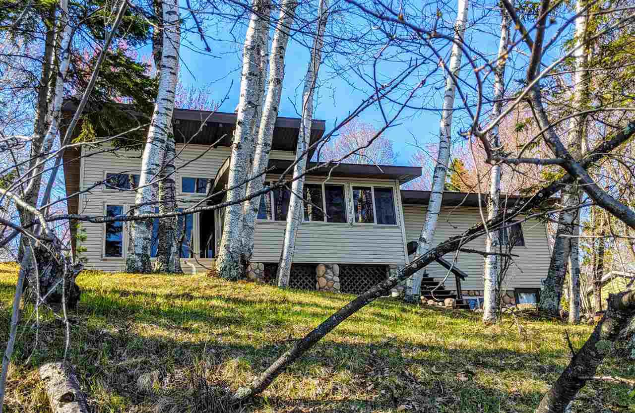 Great Phillips Chain of Lakes find! This property offers end of road privacy on a wooded, landscaped lot with level, SANDY swimmable frontage. This part of the lake has scenic islands and a depth of about 11 feet in front of the house, making for some great fishing right off the dock. Relax at the fire pit down by the lake or enjoy panoramic lake views from the insulated 3 season room or Great Room with floor to ceiling windows. The living area is open, with vaulted ceiling and large wood beams. The kitchen has custom cabinets, pantry, large counter with seating, and upraded appliances. Two of the Three bedrooms have 2 sets of closets, and the lower level walk out has a workshop and plenty of space for storage. There is an oversized one car detached garage and the lot is fully landscaped with perennials, with a fenced garden and kennel. Put this on your must see list!