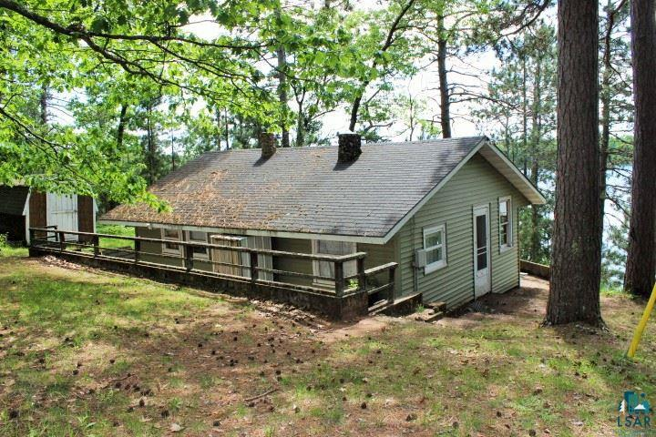 Charming rustic 2 bedroom cabin on 6 wooded acres with apx 135' of frontage. Sandy swimming frontage with afternoon sun. Cabin features wood fireplace and deck. Included are storage shed & bunk house.