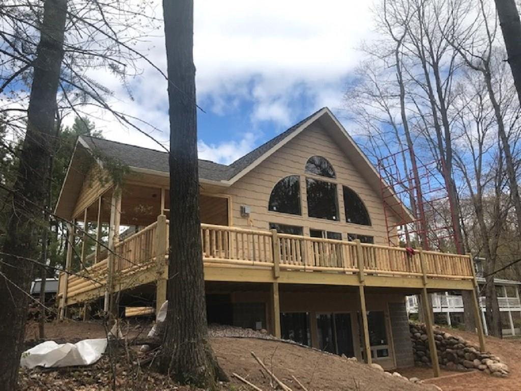 Almost complete! Brand New Log- Sided Chalet on a premiere crystal clear Lake. Has 4+bdr/3bath with loft & full finished walkout lower level. Kitchen has custom hickory cabinets, pantry, stainless appliances with granite countertops- all on solid oak flooring. Master bedroom and bath, lakeside deck, screen porch & central air. Walkout basement with an easy walk to the lake with NO steps to your south-facing sugar sand frontage. Nicely treed with majestic pines & hardwoods  Circle drive, log accents, wet bar & 2 freestanding gas log fireplaces are a few more amenities.. Whitefish lake is a deep clear and good size lake for recreating, fishing or take a fun boat ride to Beechmoor Restaurant. A quick drive to Spooner, Hayward or Rice Lake, & only about 2.5 hours to twin cities area. (Still under construction- should be complete in plenty of time to start enjoying summer lake life)!