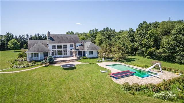 Seeking a Weekend Retreat or Large Family Estate? THIS IS IT!Huge Prairie Style Farmhouse on 178 acres, located just minutes from Lake Geneva, 1.25 hours from Chicago and an hour from Milwaukee. This beautiful 7-bedroom, 8.1-bath hillside homeoffers the ultimate in family retreats! In-ground pool, large patio with outdoor grill and fireplace, pond, creek, 12-stall custom built horse barn which will rival any barn in Kentucky and over 100 acres of mature woods with several paddocks and significant trails (horse, snowmobile, ATV and walking trails). This property offersan opportunity for those with even the most serious equestrian and outdoor interest. An adjacent caretaker home could also be available. Please request a brochure with list of extensive home and property features.