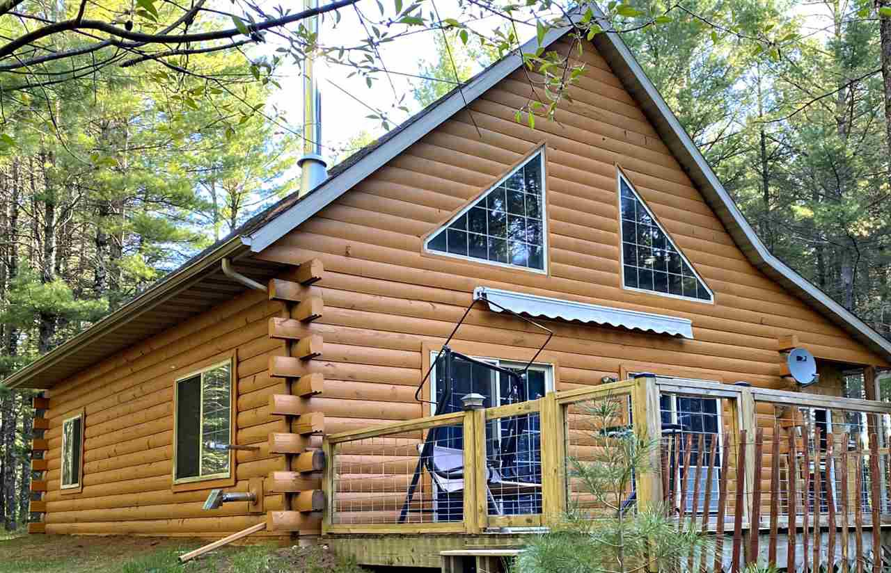 1.5 story log home on over 2 wooded acres within walking distance to the Menominee River.  Property borders Wis Electric rec land.  Master bedroom and bath on the main level with a large loft bedroom on the upper level.  Open concept living room and kitchen featuring tongue & groove woodwork.  Enter into a 7x21 screen porch and then move to the 14x24 south facing deck with a retractable awning.  Property also includes two storage sheds
