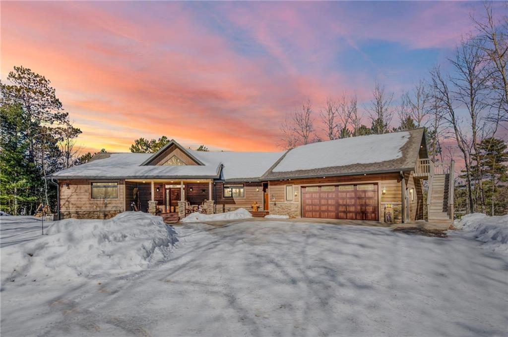 This custom built house sits perfectly in to the landscaping overlooking the Upper Eau Claire Lake. As you walk thru the solid carved front door, the huge vaulted ceiling lead to a panoramic view as far as the eyes can see. In this stunning home, no detail has been overlooked. From the high end windows, granite island and kitchen counter tops with an island Teppanyaki grill and separate induction heat stove that has a built-in electronic exhaust fan. Double oven, heated floor in the garage and basement. Bar top and table imported from Mexico with a copper finish. Built in wet bar with three door cooler. Attached bunk-house over the garage with a bathroom that holds 10 people easily. 150 feet of shoreline, two dock and a boat lift. Plus, much much more!