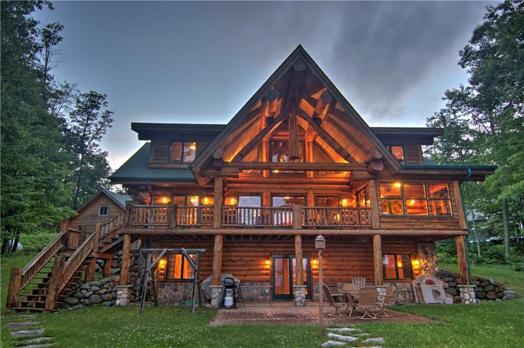 """Custom built, hand carved 18"""" dead standing pine log home on low elevation private lot at the end of the cul-de-sac. South easterly big lake view and sandy bottom at water's edge for great swimming in this clear water, Grindstone Lake. Many hand hewn features including an eagle at the roof peak. The open concept accentuates the massive log features in the home. Main floor master suite on lakeside. 3 season porch and large deck for entertaining. The lower level walk-out includes a bar and entertainment area."""