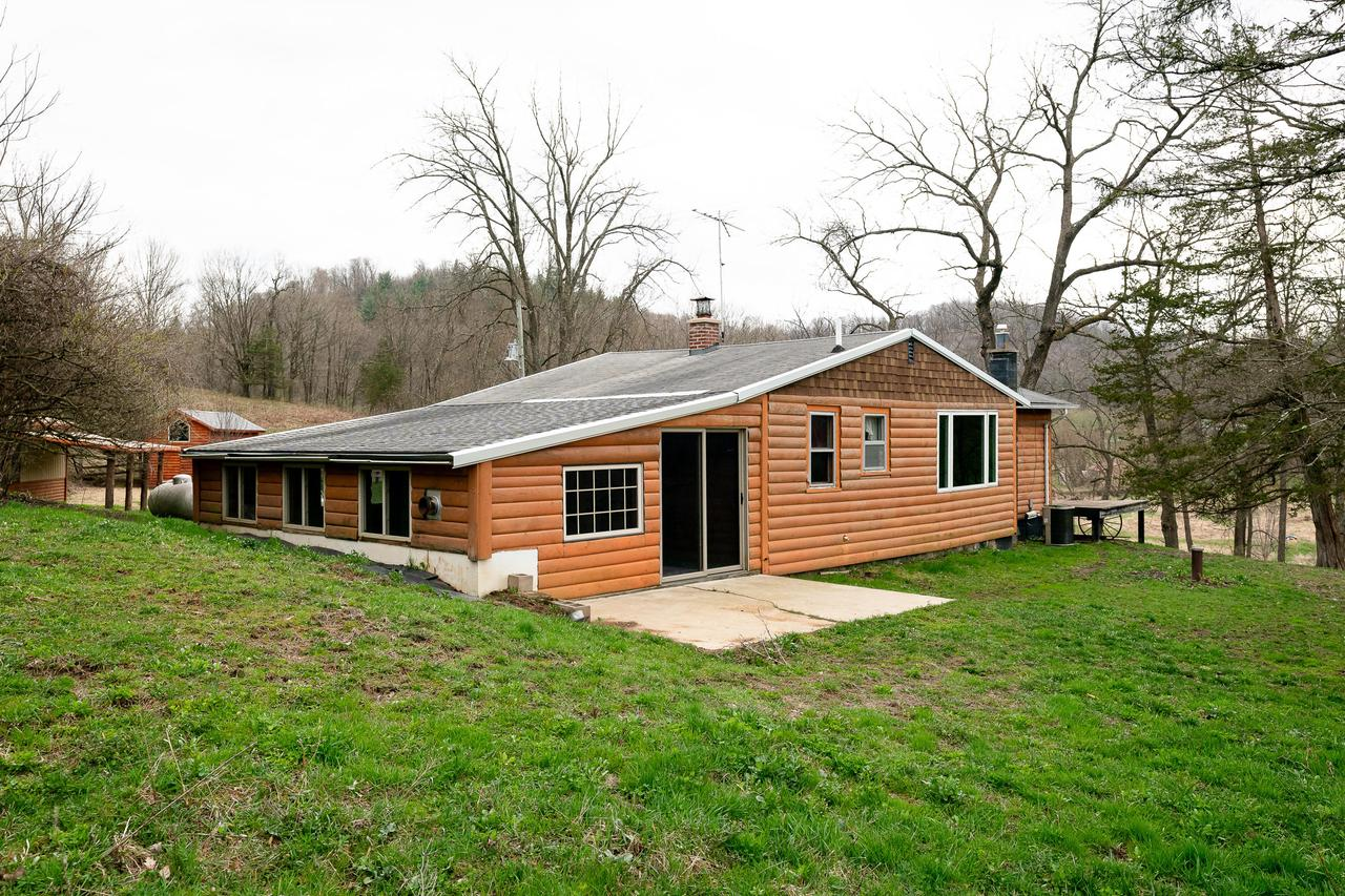 This property is located right next to the Kickapoo Valley Reserve and just minutes away from the Wildcat Mountain State Park, horse trails, Class A trout fishing, hunting and canoeing!  A year-round flowing artesian spring, hand-pump and small pond highlight the gently rolling landscape.  This property features a log-sided cabin on a dead-end road with a 2 car detached garage, barn/shop and four-season mud room added in 2013.  Modern amenity updates include: new 200 amp electric service, PEX-water piping with isolation valves, R-25 insulation in the ceilings, central air, forced air LP gas heat with high efficiency furnace, therapeutic whirlpool tub, high speed internet, partial basement, hardwood floors and separate laundry room.  Must see!