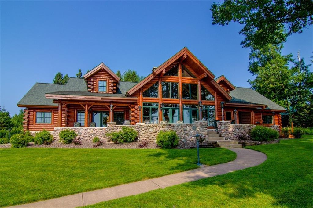 Chippewa Flowage--Spectacular custom log home on Moore's Bay offers the best of all worlds: exceptional design & quality, 424 feet of level shoreline, and stunning easterly views overlooking charming islands. The 6 BR, 6.5 bath home features an open floor plan including a stately living room with stone fireplace, large kitchen with ample storage and dining room with plenty of space for gatherings. Enjoy your privacy in the owner's suite which includes lakeside bedroom, an office, a storage room, and a sun room. Another wing includes 4 additional bedroom suites. The lot is one of a kind with an easy approach to a level, sandy shoreline, a working boat house, a private boat launch. Excellent storage with the 2 car attached garage and the 40x60 det garage. The property also includes a 1.5 acre off-water developable lot. Watch the video for more!