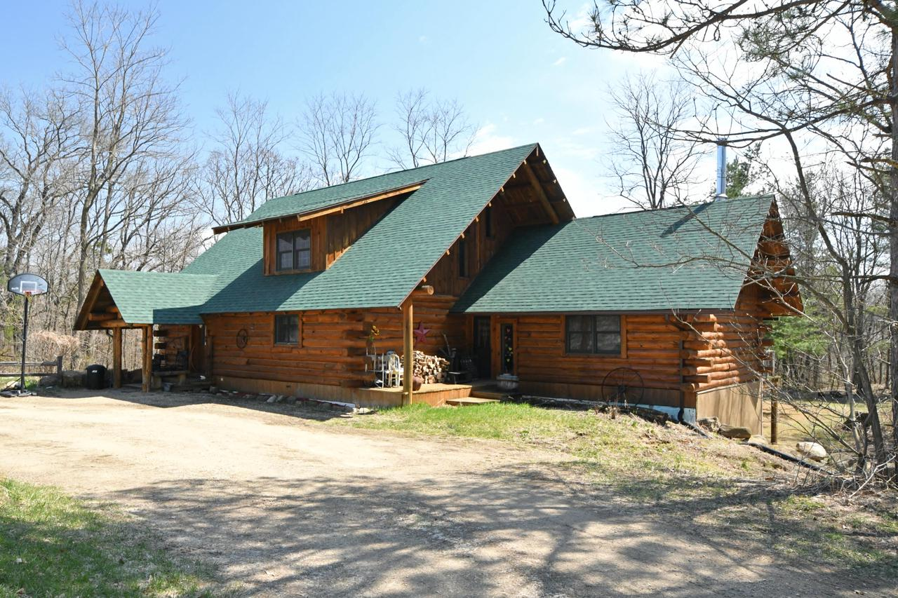 If owning a log home is your dream -Opportunity awaits! This full log quality built home is a must see set on 160+/- ft of the Montello River. Wildlife galore, nature is calling from this 10+/- acre property with a pole barn. Home offers a cook's delight kitchen with lots of added features, 3 bedrooms, 2 1/2 baths, vaulted ceiling with massive wood burning field stone fireplace, large beams and in-floor radiant heat. Lower level has an unfinished walk out family room, and over sized garage. Property is zoned for horses & barn. There is also a 6-person spa on the deck for your outdoor enjoyment. Must see - Call today!