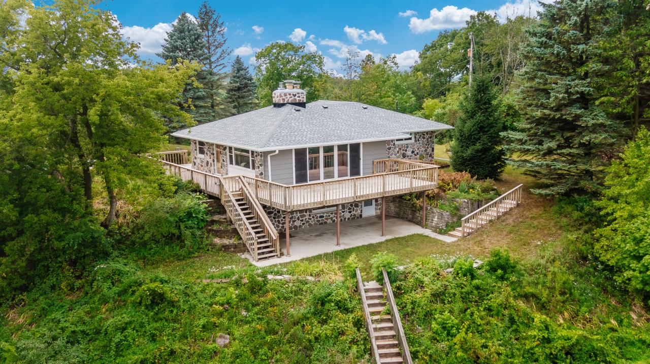 You're going to be wowed by this completely remodeled home. Sitting on 4.47 acres is a walk out ranch with brand new kitchen, baths, LVT flooring throughout, all new windows, new roof, new AC system, brand new appliances, fixtures and the list goes on. Main level has natural stone fireplace for those chilly fall and winter days. Lower level is a walkout and has rec room with gas fireplace for extra living space, huge laundry, office or possible 4th bedroom, and half bath that has possibility for full bath. The views are incredible from the huge deck that wraps around on three sides of the home. This is truly a gem and should not be missed!! If you like racing or skiing, Slinger Speedway and Slinger Ski Hill are both less than 1 mile away. How convenient is that?!