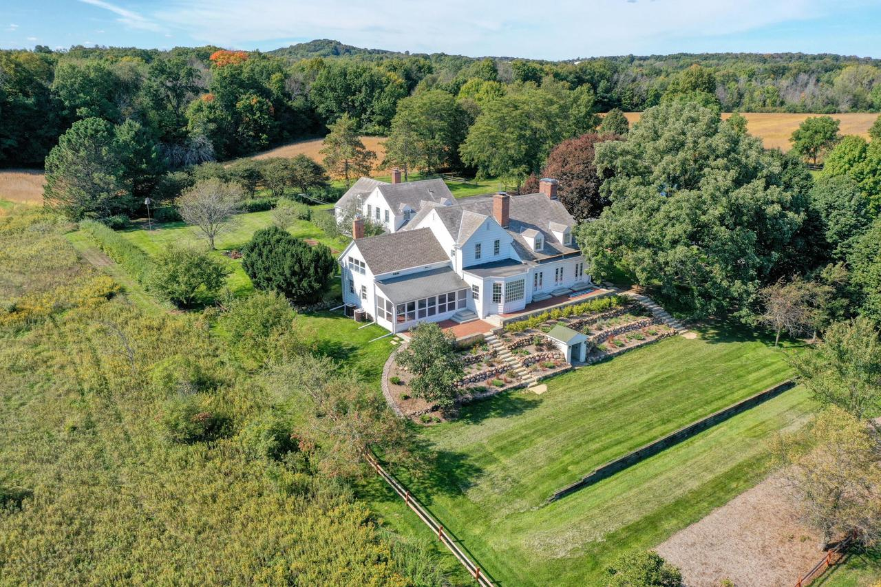 Ridgefield Farm near Holy Hill spans over 70 acres with scenic tree-lined fields, classic dairy barn, large machine shed, beautiful historic home complete with an adjoining guest cottage. Very private, set back 1/2 mile off the road. Picturesque grounds feature a brick patio overlooking tiered flower garden, lovely sunroom with brick floor and a wall of windows, and a quaint greenhouse off the breezeway. The original 1900 home was added onto and remodeled in 1930 and 1960.