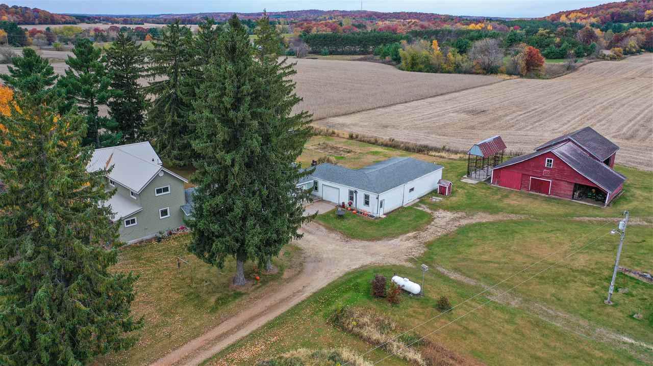 Fully updated farmhouse with views that go on forever. Great hobby farm option. Barn, shed and large garage area for excellent storage. Walk into a large foyer with laundry and full bath. Up a few steps to a large farmhouse kitchen, dining room and dining area and living room. Huge bedrooms on upper level. Heat with exterior wood boiler and Lp furnace for back up. Great commute to the Waupaca and Iola area. Water Softener, Lp Tank included in sale along with appliances. Move in ready!