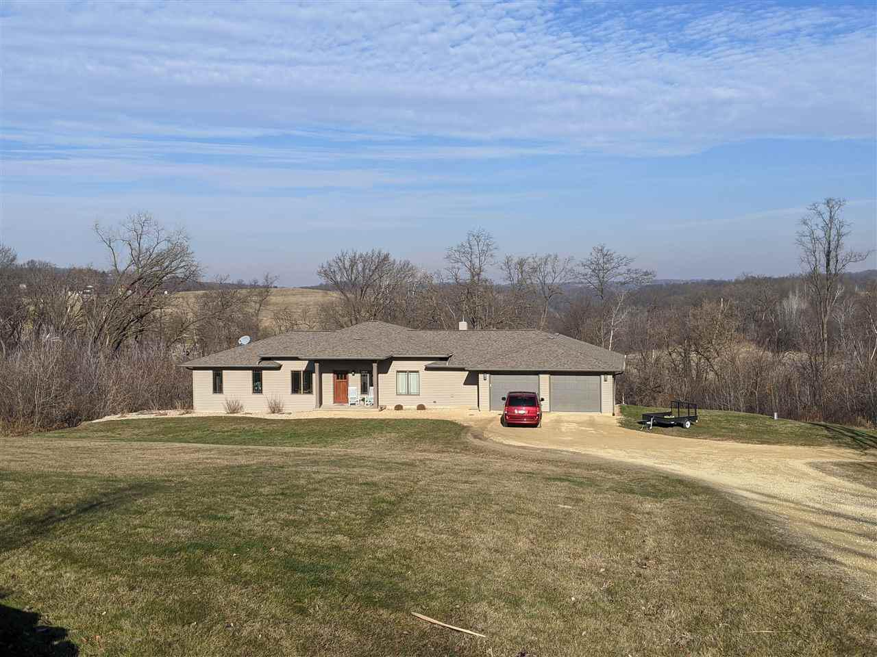 What a A Country Dream! Work from home in your own paradise! A must see custom home on 20 acres has it all. Open concept w/10 ft ceilings and floor-to-ceiling windows that provide natural light and views for days. The kitchen offers an oversized island, stainless appliances & walk-in pantry. Formal dining or office space has french doors for privacy. Main bedroom includes walk in closet and bath with dual sinks.Hardwood floors and antique farmhouse solid wood doors add special character to this home. Walk-out basement offers finished family room, a 3rd bed, full bathb & work-out area.  Outside: lrg heated garage w/running water,  raised garden beds, fire pit, trails thru the acreage AND 3 tree stands! 7 acres tillable that can be rented.
