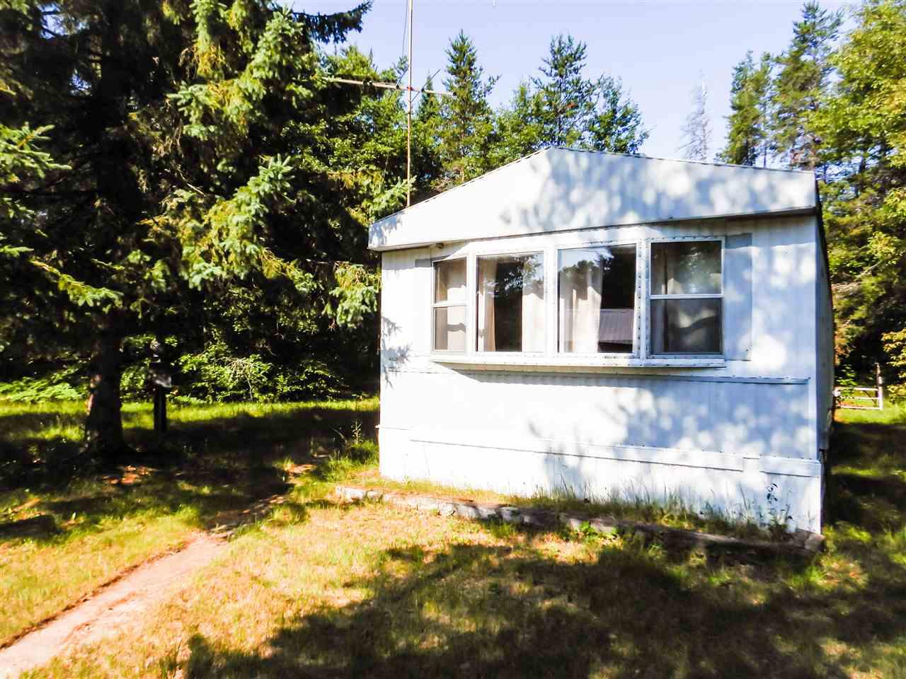 Almost one Acre of partially wooded land right off of Hwy 141. 0.8 Acres. Old Mobile home in need of much repair or just remove from property. Property does have a well. Septic set up for mobile home. Possibilities are endless with this little piece of land. Come check out today!
