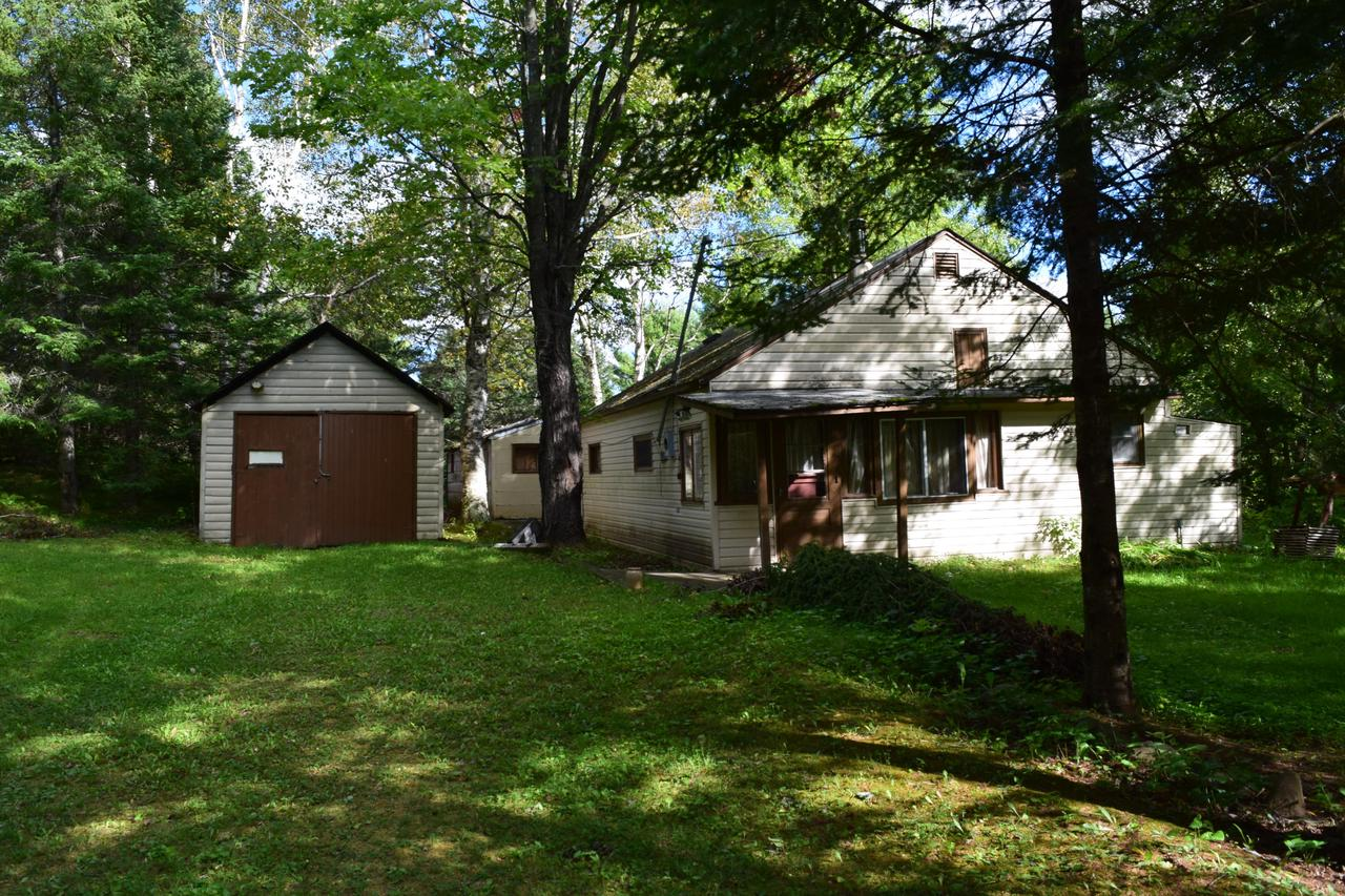 This affordable two bedroom cottage/cabin located near Oconto River sits on a dead end road. The open concept living/kitchen/foyer area welcomes you and your family to your new home.  The enclosed loft area has room for additional sleeping. The garage and shed are perfect for your toys.  This home is located close to water and easy access to the ATV/snowmobile trails. Motivated seller.  Property is being sold ''AS IS'', seller has located the septic system and has had it tested, it is in good to fair condition. The recent storm caused some damage to the electric coming into the house and we are working on getting that repaired as soon as we can get an electrician to the house.