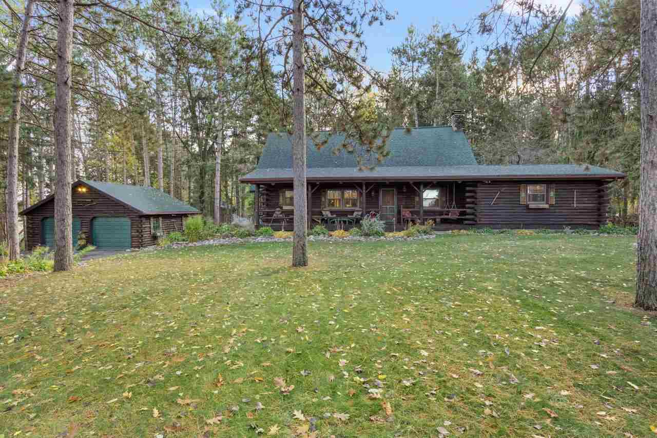 Beautiful 1.5 story log home, located on a private and wooded 1.66 acres. Home offers 3 bdrms and 2 full baths. Updated kitchen with custom cabinetry, granite countertops and SS appliances that are all included. Open floor plan that shows off the great room with a floor to ceiling stone, wood burning fireplace and vaulted ceilings. Master Bedroom on the main floor and large office/den right off the kitchen. 3 seasons room. 2 horse stalls and oversized, heated and insulated outbuilding. Relax and enjoy your time on the large deck with hot tub.
