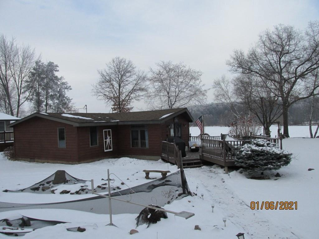 Looking for that cozy lake home, here it is!  Just steps from the lake with beautiful views of the water.   Home features newer cabinets, countertop, all buildings professionally stained 2020, decks stained in 2020, new dock boards 2019, 16 X 22 shop, sprinkler system, roof approx 10 years old.   36 X26 Garage, 16 X22 Shop.  Interior of garage is finished off with car-siding, includes a portable bar, stove & refrigerator.  Solar powered boat lift negotiable.